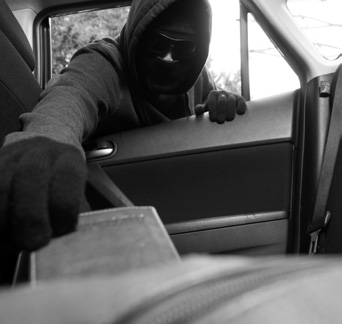 Man taking purse out of a car with a ski mask on