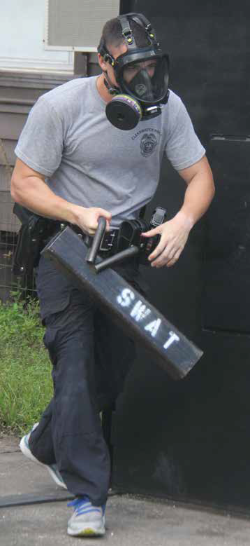 Man carrying SWAT equipment and gas mask
