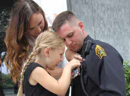 Woman and child pinning a badge to a police officer