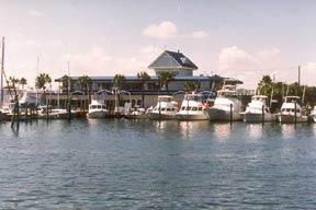 Photo from over the water facing the Beach Marina Building on a sunny day with several fishing vessels docked in the foreground.