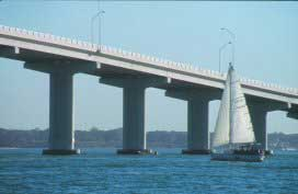 Image of sailboat passing under U S Highway 60 causway bridge