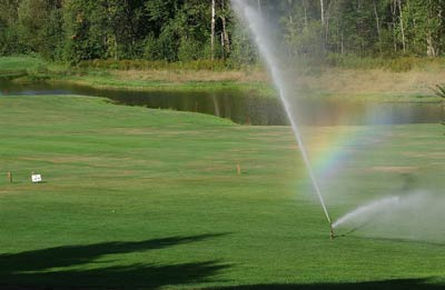 Image of sprinklers running on a golf course
