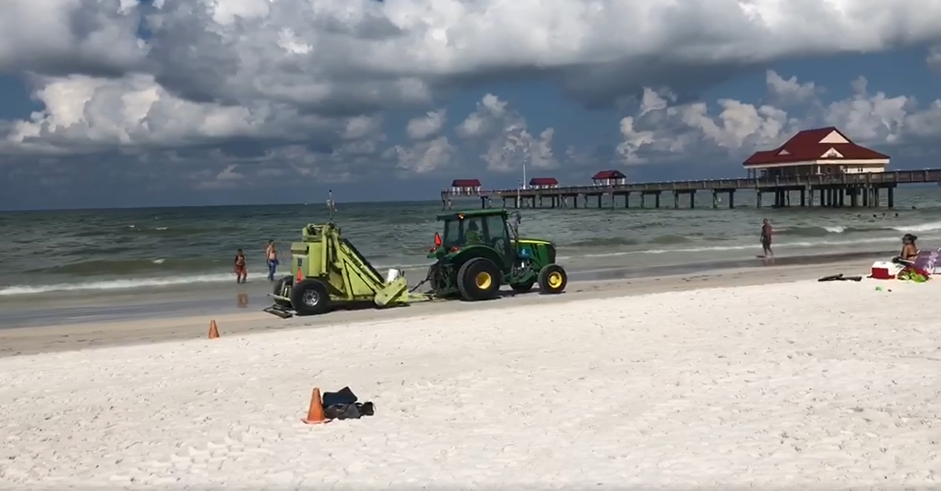 Image of tractor and beach cleanup machine dealing with Red Tide dead fish