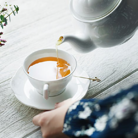 Person pouring water into tea cup
